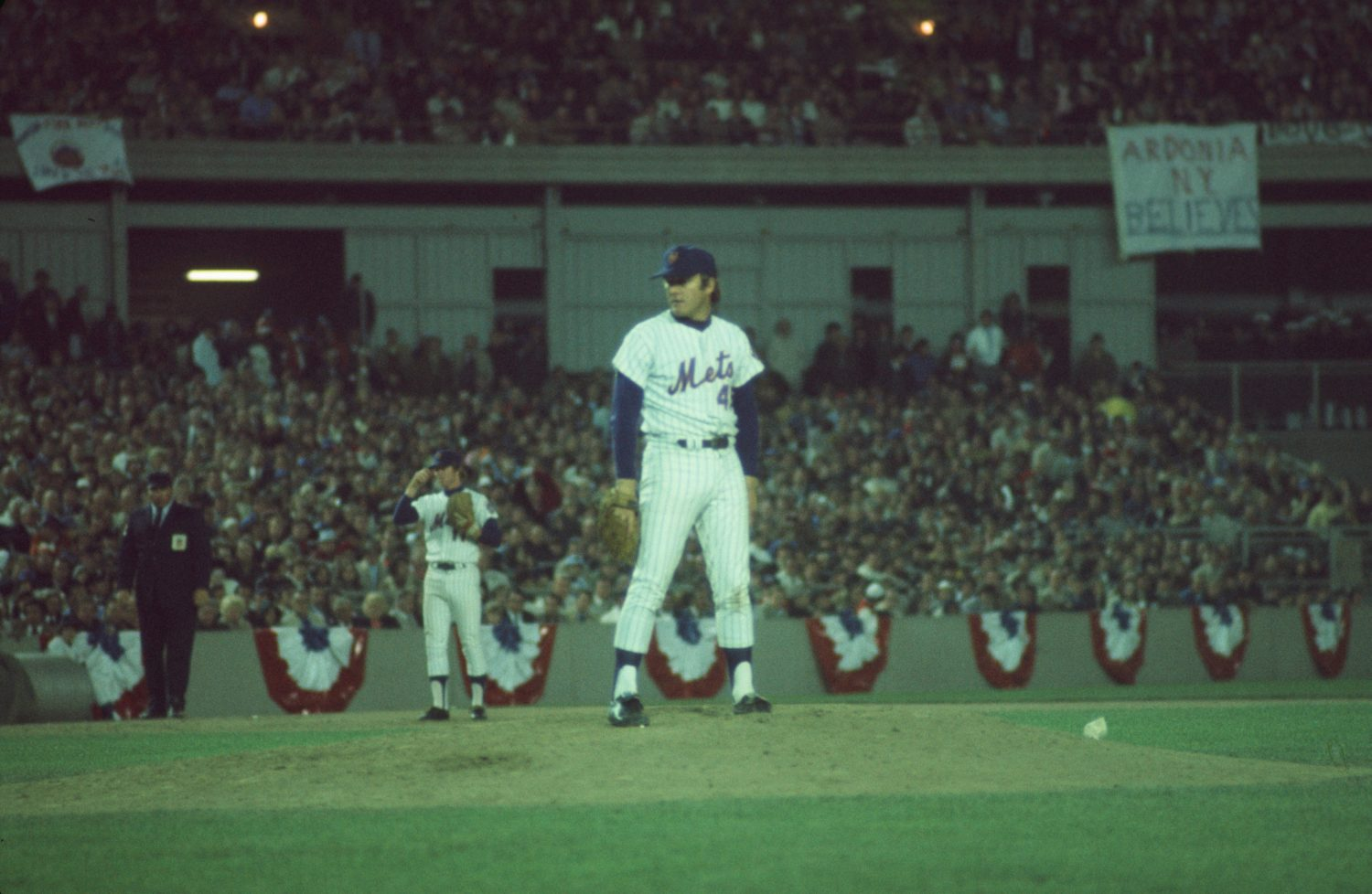 Wayne Garrett on the Mound as Sign in Background Reads