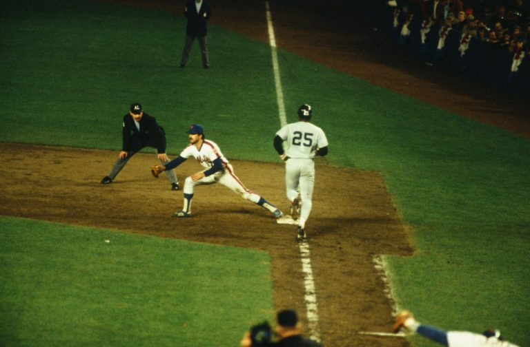 Keith Hernandez's stretches at first base to catch a ball as a runner touches the bag.