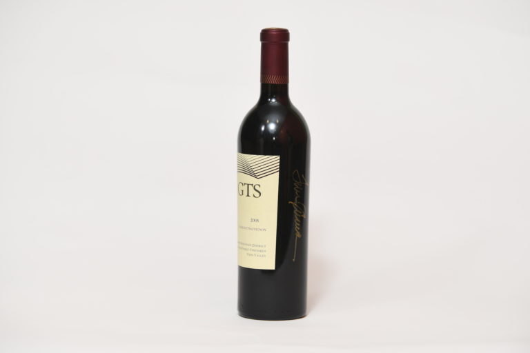 Side-view with wine bottle with signature that reads
