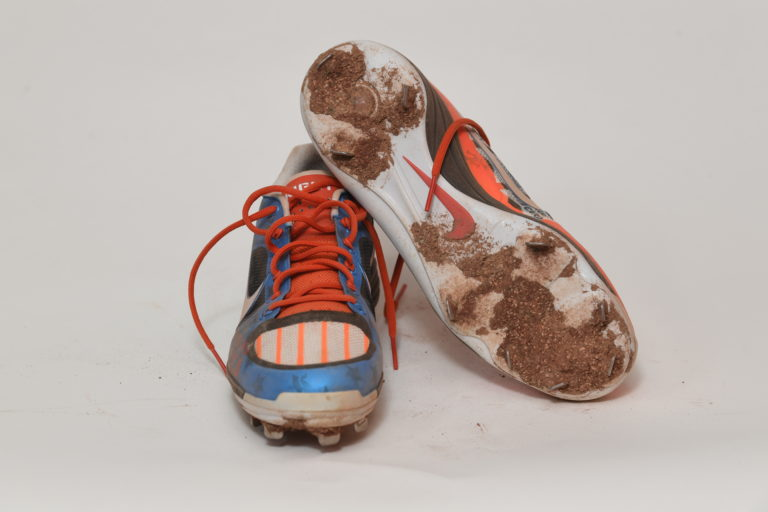 The underside of a cleat with clay on it propped up on a blue cleat